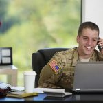 Military personnel with computer in office